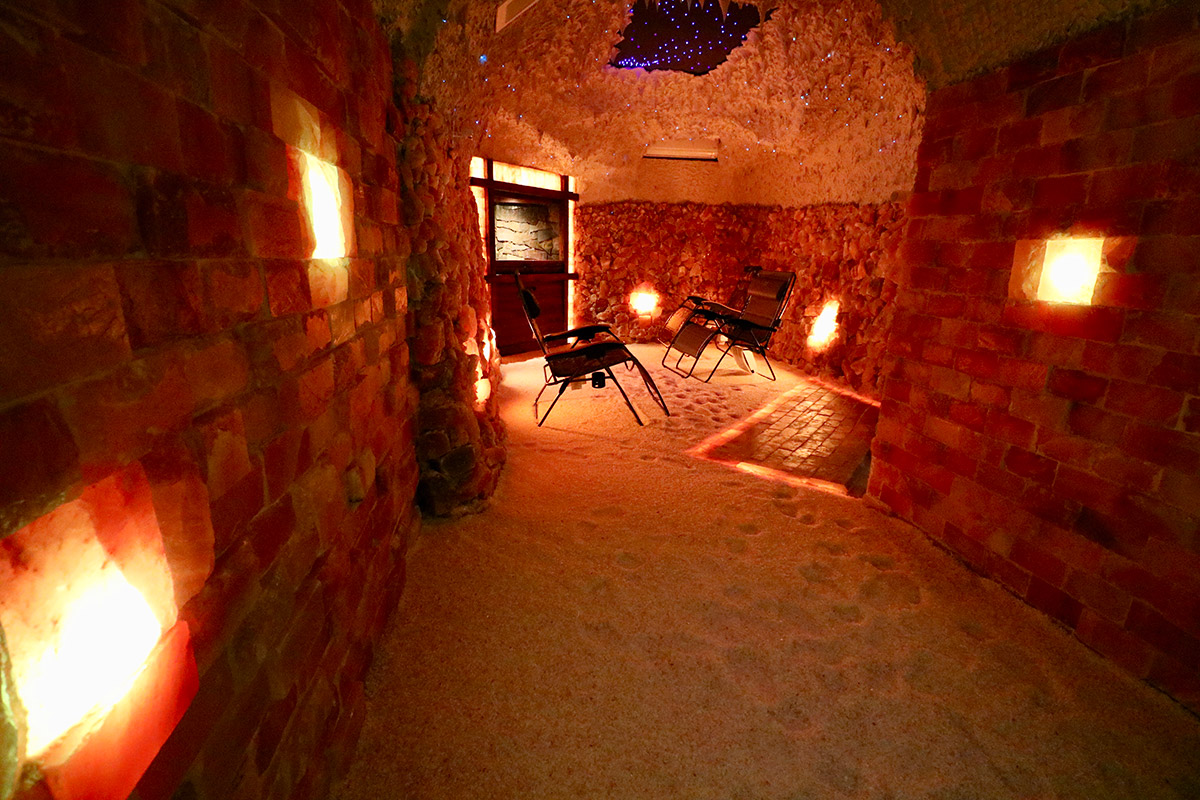 A salt cave includes rustic elements such as salt boulders, natural finish bricks, a water cascade and skylight