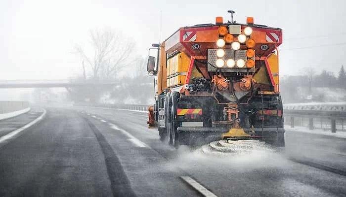A salt truck de-icing a highway